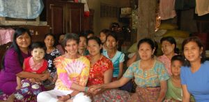 Portrait of poet and photographer, Melody Mociulski with a group of women in colorful attire in Bago, Myanmar.