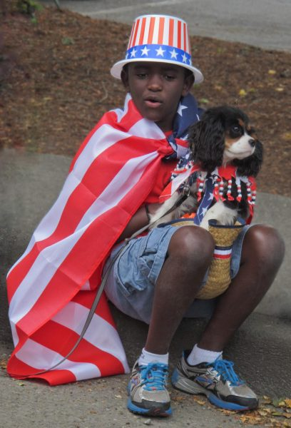 African American boy wrapped in American flag holding and Cocker Spaniel dog